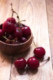 Freshly washed cherries in wooden bowl stock image