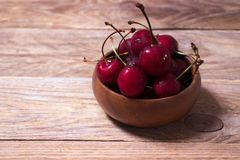 Freshly washed cherries in wooden bowl royalty free stock images