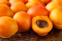 Freshly washed, ripe half sliced and whole apricots on a black cutting board with water drops and reflections Stock Image