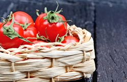 Freshness cherry tomatoes in a wicker on a wood background Royalty Free Stock Photography