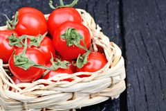Freshness cherry tomatoes in a wicker on table Stock Photos