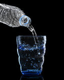 Freshness cool and clean drinking water pouring to blue glass is Stock Image
