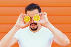 Freshness and healthy lifestyle: portrait of handsome sexy man with beard hiding eyes behind sliced oranges like sunglasses royalty free stock images