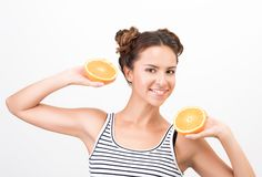 Freshness and vivacity. Joyful young woman holds halves of orange. S. White background stock photo