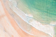 Freshwater beach aerial shot waves on beach. Freshwater beach waves with morning sunlight hitting the water. Seagulls play in the shallows stock photography