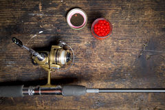 Freshwater rod and reel with bait. A spinner rod with salmon eggs on a wooden work bench Stock Image