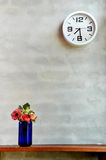 Freshy Morning. A photo of an analog clock on the grey stone wall with a vase of flowers Royalty Free Stock Photography