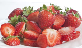Fresly picked strawberries on a plate. Some freshly picked strawberries, whole and sliced on a plate stock photography