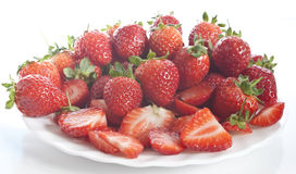 Fresly picked strawberries stacked up on a plate. Some freshly picked strawberries, whole and sliced stacked up on a plate stock photography