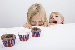 Frestade barn som ser muffin på tabellen royaltyfria foton