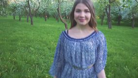 Frestande körningar för ung kvinna i en äpplefruktträdgård blommar på våren vit Stående av en härlig flicka i aftonen arkivfilmer