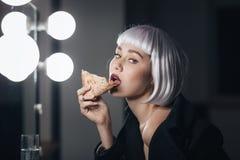 Frestande kvinna i blond peruk som äter pizza och dricker champagne arkivfoton