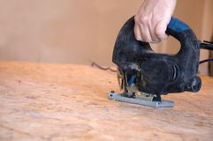 Fret-saw. Worker's hand holding and electical fret-saw working Royalty Free Stock Image