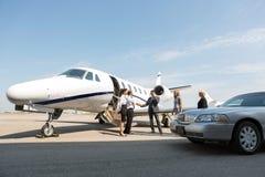 Företags folk som hälsar airhostessen och piloten At Arkivfoto