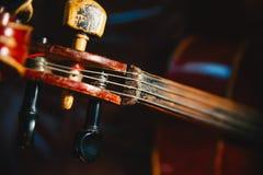 Fretboard и настраивая колышек старой затрапезной виолончели на черноте Стоковая Фотография