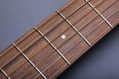 Fretboard auf Akustikgitarre-Nahaufnahme auf fünftem Gitterwerk Stockfoto