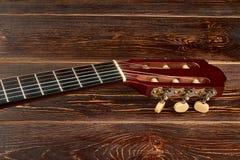 Fretboard av gitarren på träbakgrund arkivfoto