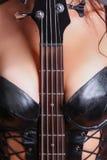 Fretboard de la guitarra intercalado entre sus pechos Imagenes de archivo