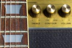 Fretboard de la guitarra y detalle del marcador del traste, botones viejos borrosos del amplificador en el fondo foto de archivo libre de regalías