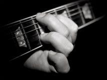 Fretboard del giocatore di chitarra che gioca il nero delle corde Immagini Stock