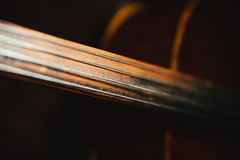 Fretboard of old shabby cello on a black backgrounds Royalty Free Stock Photos
