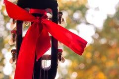 Fretboarden av den klassiska gitarren med ett rött band på blurr Royaltyfria Bilder