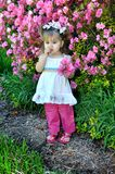 Fretfull and Worried. Little girl stands chewing on her thumb and worrying.  She is besides an azalea bush filled with pink flowers.  Child is hold a small Stock Image