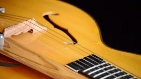 Frets, string, body, mouth and bridge of typical classic spanish guitar gyrating. Classic Electric Guitar Jazz Rotating in Horizontal stock footage