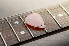 Frettes de guitare avec le médiateur sur des ficelles image stock