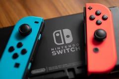 Freude-Betrüger, die Nintendo-Schaltersteuerung, wurde neben dem Nintendo-Schalter-Logo gesetzt lizenzfreies stockbild