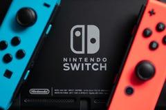 Freude-Betrüger, die Nintendo-Schaltersteuerung, wurde neben dem Nintendo-Schalter-Logo gesetzt lizenzfreies stockfoto