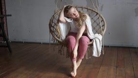 Freudenkonzept, schönes junges blondes Mädchen mit einem Plaid auf ihren Schultern, die das Schwingen im gemütlichen Dachbodenrau stock video footage