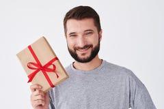 Freudig erregt bärtiger Mann im grauen T-Shirt, das Präsentkarton hält Stockbild