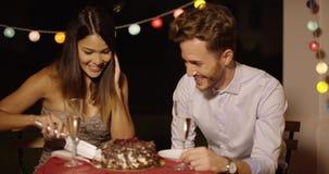 Freudig erregt junge scherzende Paare, wie sie den Kuchen schnitten stock video