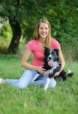 Freudige Frau im rosa Hemd und in den Blue Jeans, die mit ihrem weißen und schwarzen Hund im Park während des sonnigen Sommertage Stockbilder