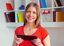 Frau, die den Tablette-PC hält und Kamera betrachtet Stockfotografie