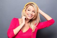 Freudige junge Frau, die Musik auf orange Kopfhörern hört Lizenzfreie Stockfotos