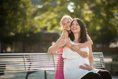 Freudige Mutter und Tochter draußen Familienabbindenkonzept Stockfoto