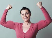 Freudige schöne Frau 40s, die oben ihre Muskeln biegt Stockbild