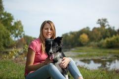 Freudiger Brunette, der draußen mit mit ihrem weißen und schwarzen Hund im Park während des sonnigen Sommertages spielt Stockfotografie