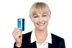 Freudiger weiblicher Angestellter, der Kreditkarte zeigt stockfoto