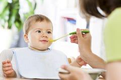 Freudiges Baby, das Lebensmittel essend beginnt. stockfotos