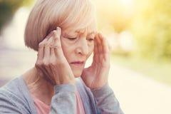 Freudlose ältere Frau, die ihre Tempel hält stockfoto