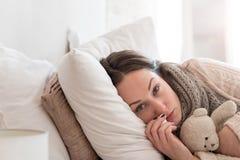 Freudlose deprimierte Frau, die auf dem Bett liegt Stockfotografie