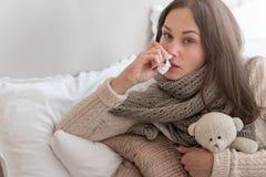 Freudlose junge Frau, die unter Grippe leidet Stockfotografie