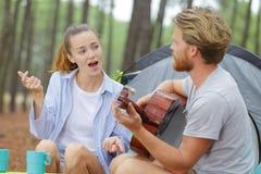 Freund, der den Gitarrenpartner singt außerhalb des Zeltes spielt stockfotografie