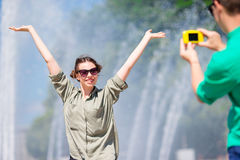 Freund, der ein Foto seiner Freundin beim Sitzen des Hintergrundes der Brunnen macht Junger Mann, der an Foto von der Frau macht Stockbilder