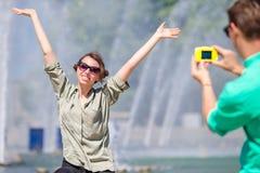 Freund, der ein Foto seiner Freundin beim Sitzen des Hintergrundes der Brunnen macht Junger Mann, der an Foto von der Frau macht Lizenzfreie Stockfotografie
