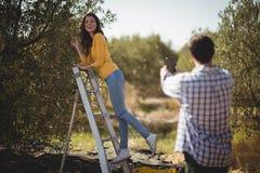 Freund, der Freundin am sonnigen Tag am olivgrünen Bauernhof fotografiert Stockfoto