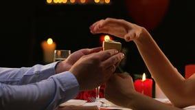 Freund, der kleinen Kasten seiner Freundin, kostbares Geschenk zum Valentinsgrußtag darstellt stock footage